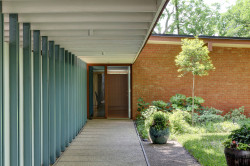 Cantilevered Roof Covers Approach to Midcentury Modern Entrance